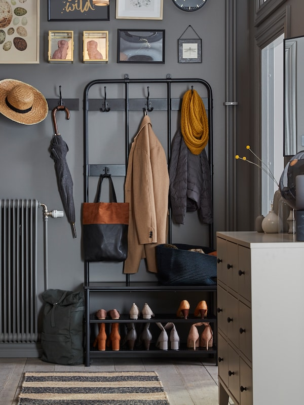 A black PINNIG coat rack with coats, shoes, a basket and a bag stands in a hall near a beige BRYGGJA chest of drawers.