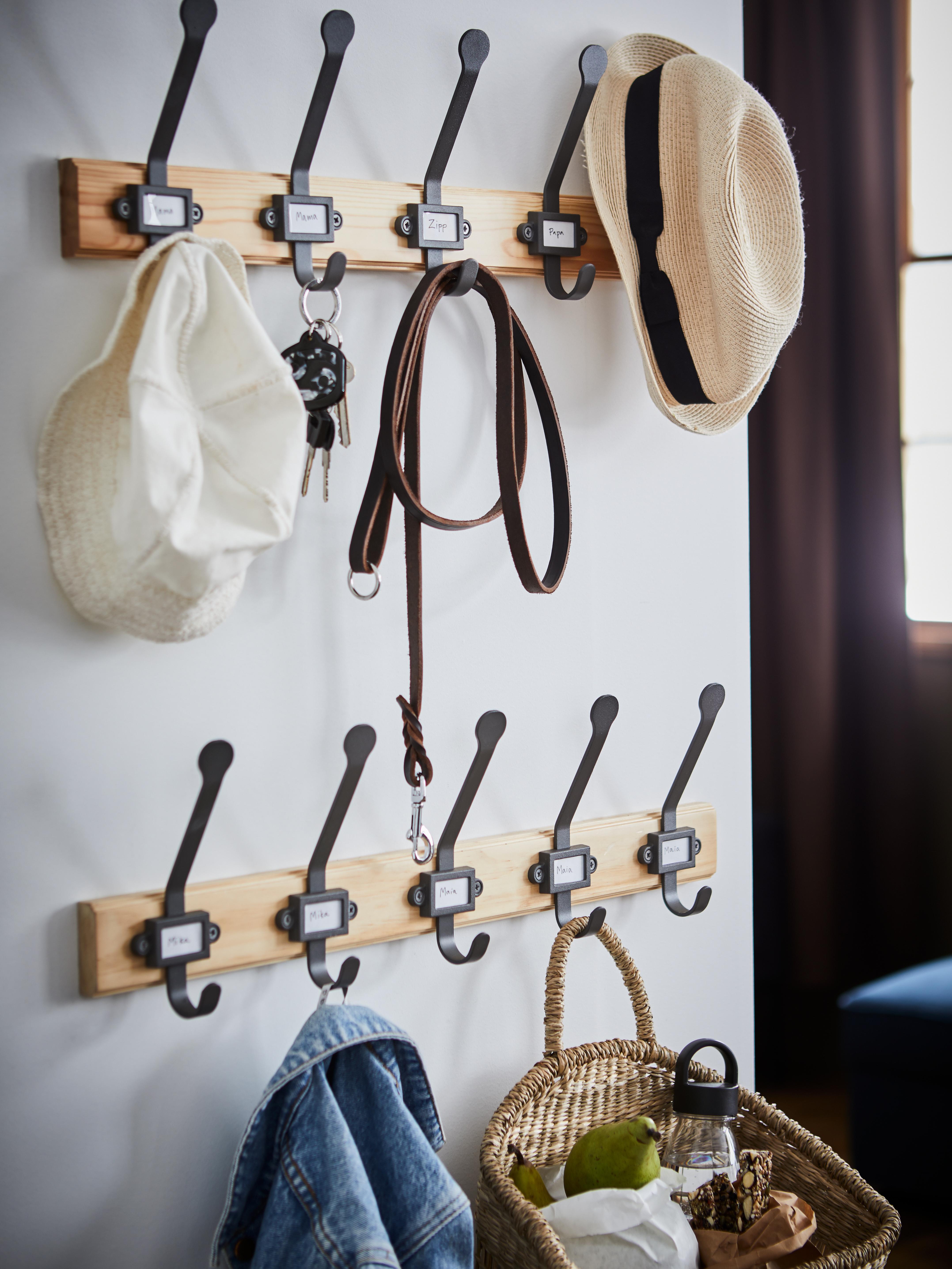 A jacket, a picnic basket, two hats, keys and a dog leash hanging on two pine/grey KARTOTEK racks with 5 hooks in a hallway.