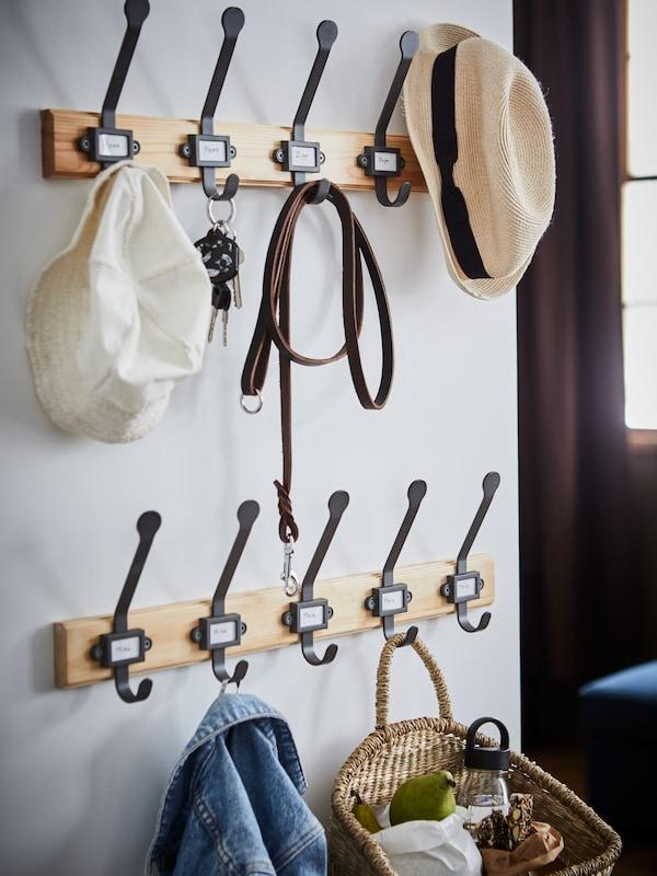 Kabát, piknikkosár, két kalap, kulcs és egy kutya póráz lóg a két fenyő/szürke KARTOTEK 5-horgos állványon a folyosón