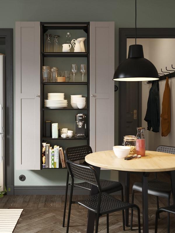 Otevřený policový díl mezi dvěma vysokými skříňkami se šedými dveřmi, kulatým dřevěným stolem, černými židlemi a černou závěsnou lampou.