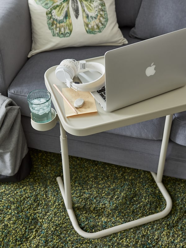 A beige laptop stand by a grey sofa, with a laptop, white headphones, pencil, eraser and a glass of water on the holder.