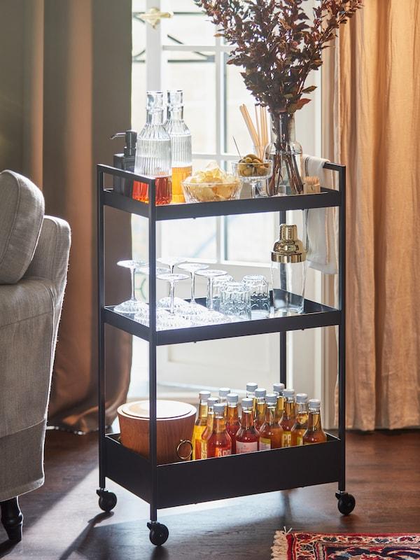 Une desserte noire utilisée comme mini-bar, avec des carafes, des en-cas présentés dans des bols en verre, des coupes à champagne et des boissons en bouteille.