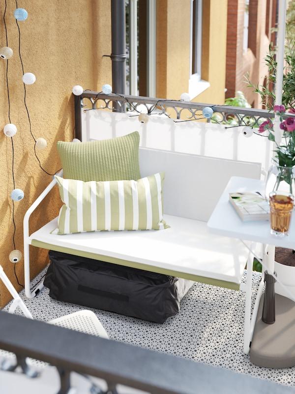 Ein kleines 2er-Sofa mit weissen Polstern und grünem Mesh mit grünen Kissen darauf. Darunter liegt eine schwarze Tasche.