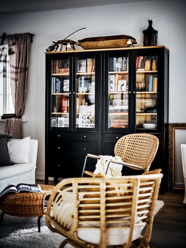 Deux vitrines HEMNES noires remplies de livres dans un salon de style campagnard, près de deux fauteuils et un canapé.