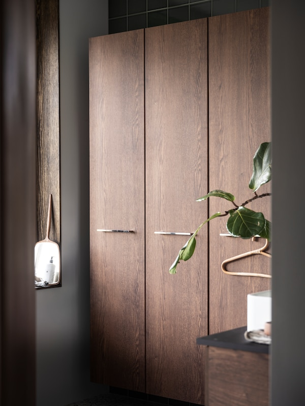 GODMORGON cabinets in brown wood with a rattan hanger on one of the knobs.