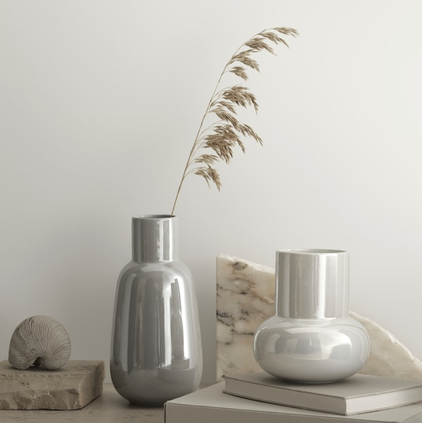 One grey and one white vase are standing against a pale grey wall. The larger vase has a stem of dried grass inside.