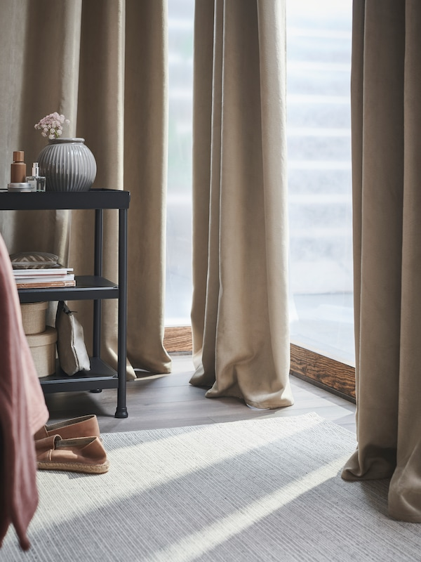 Beige BRITNA blackout curtains frame the floor-to-ceiling corner windows in a bright bedroom on a spring day.