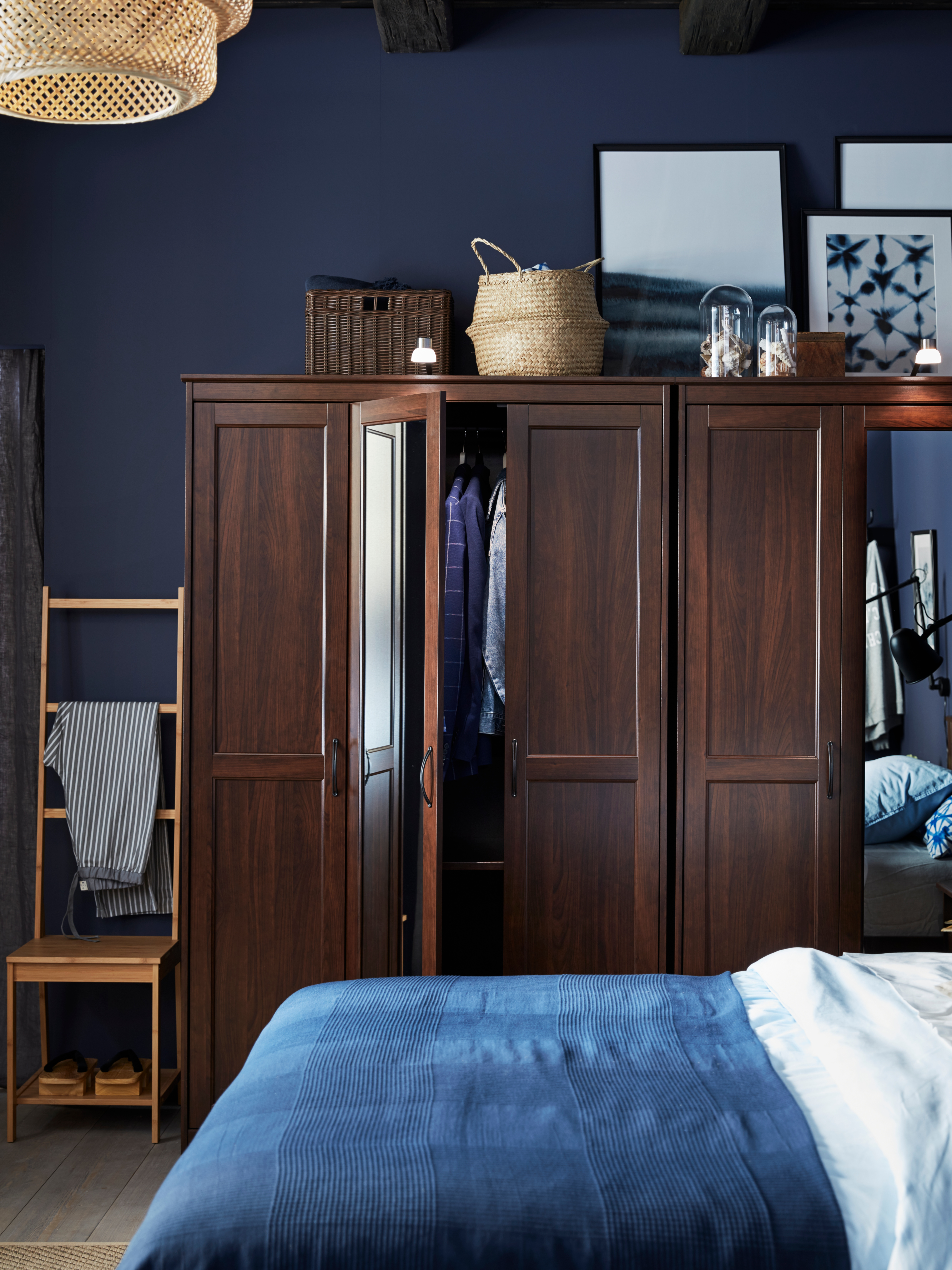 A blue bedroom wall with two side-by-side, brown SONGESAND wardrobes with baskets and art on top and an open mirrored door.