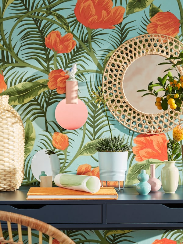 A blue ALEX desk with a book, vases and a plant on top, sits against a wall that is covered with a multicoloured fabric.