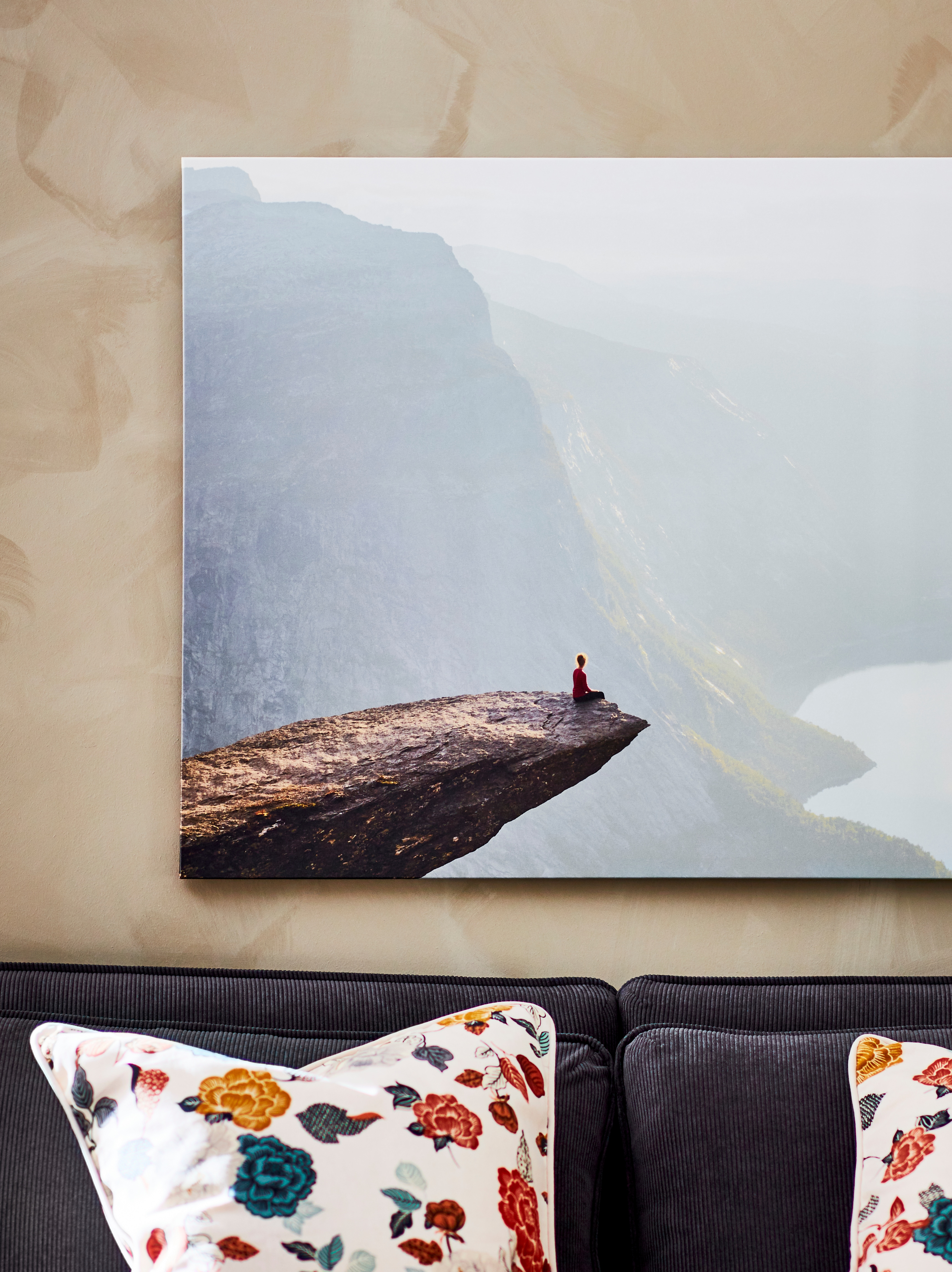 Part of a PJÄTTERYD picture of Norway's Trolltunga mountain hanging on a wall with the top of a grey sofa visible below it.