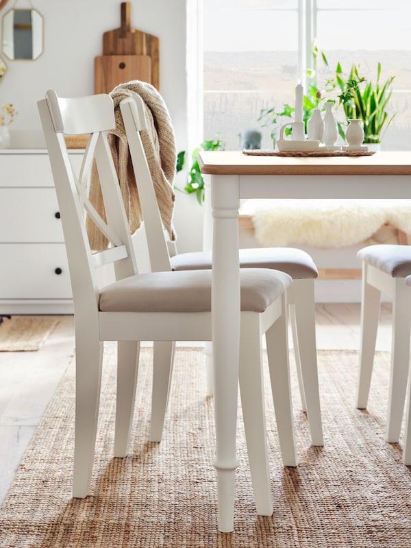 Trije beli stoli ter miza v beli barvi in barvi hrasta na preprogi iz jute.