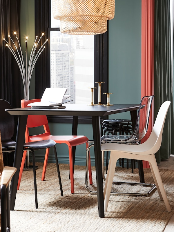 A dining area with a black table and mismatched red, white, black and transparent chairs on a jute rug.