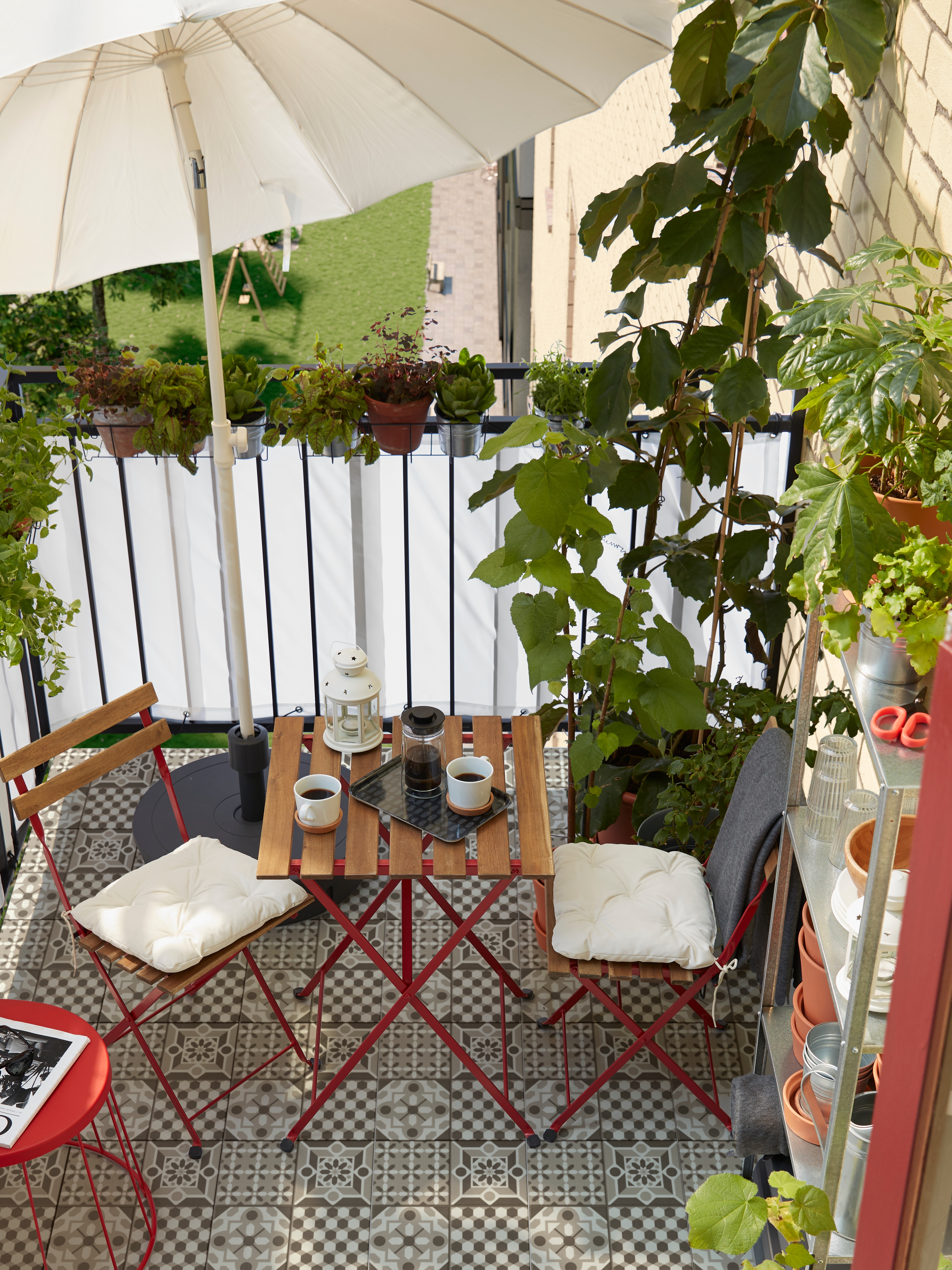 A small balcony with lots of herbs and plants, a red stool, a shelving unit, a white parasol and two chairs and a table.