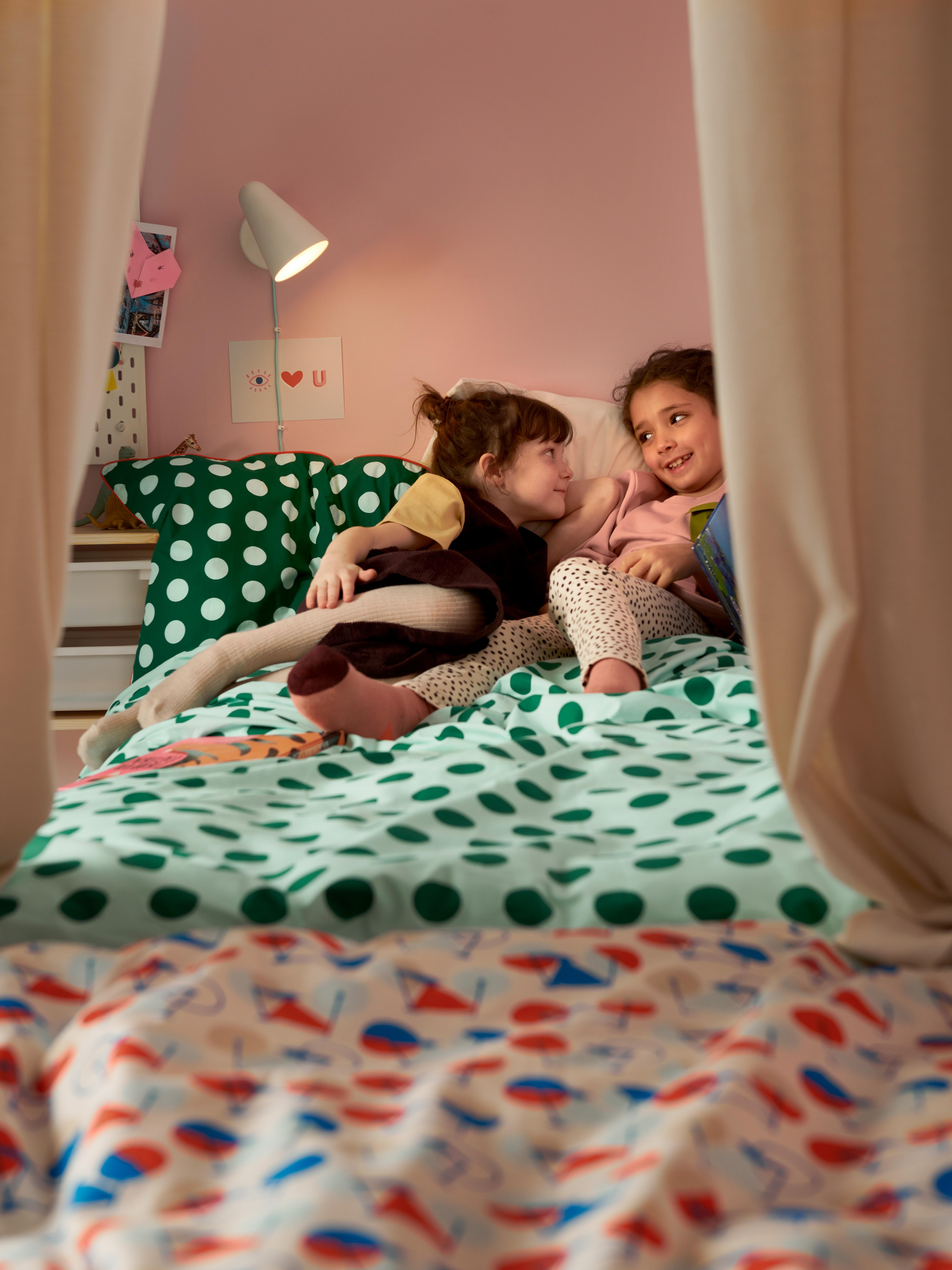 Zwei Mädchen entspannen sich in einem Bett mit bunter, grün gepunkteter Bettwäsche in einem farbenfrohen Kinderzimmer.