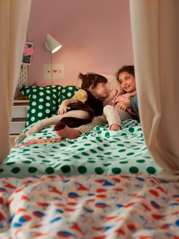 Két kislány pihen egy vidám, zöld pöttyös ágyneműhuzattal bevetett ágyon egy színes  gyerekszobában.