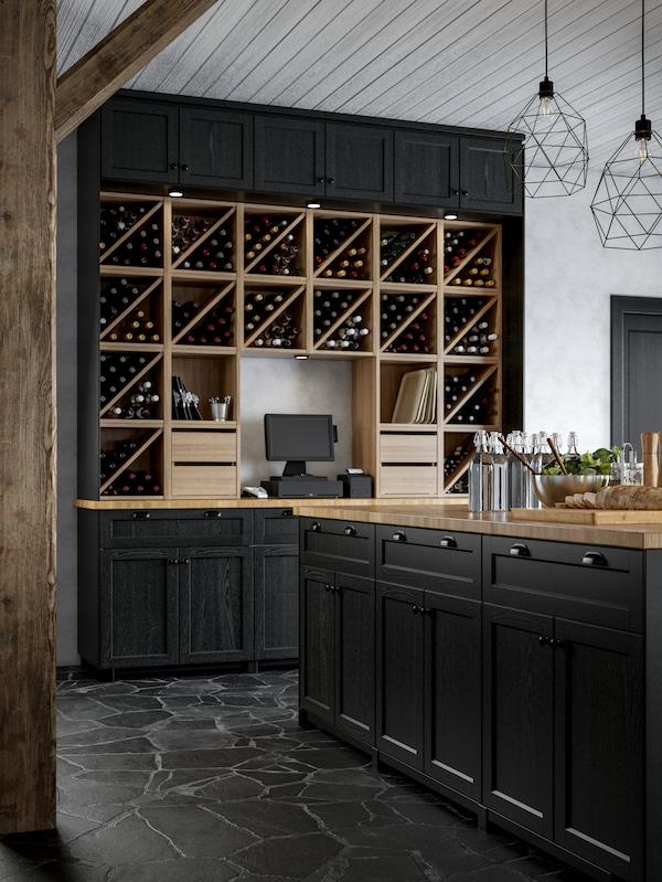Isola cucina con ante in mordente nero, scaffali portabottiglie uniti per creare una parete dal forte impatto visivo, registratore di cassa.