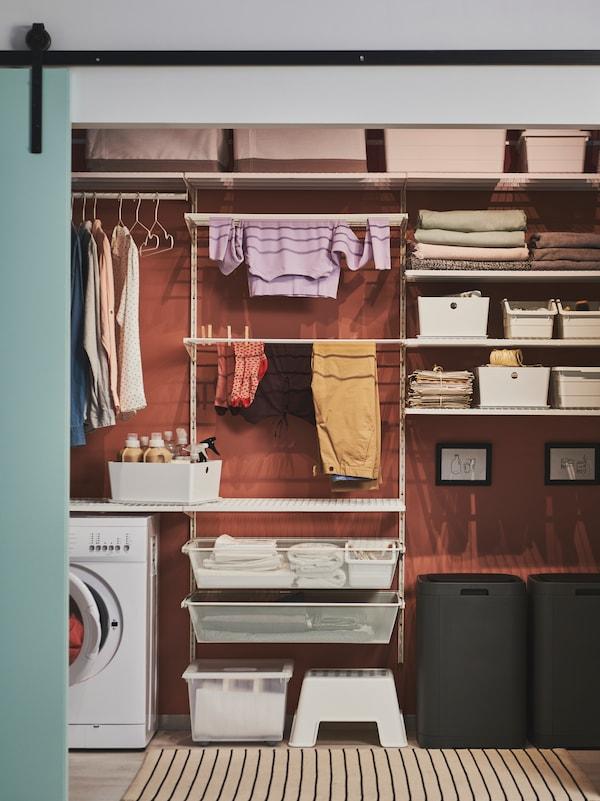 Prádelna s úložným systémem BOAXEL, na kterém jsou zavěšené šaty, uložené různé druhy krabic, složené ručníky a další věci.
