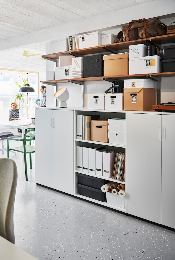 An office with closed storage and shelves holding boxes, files and diverse items. Work desks and a chair are in front.