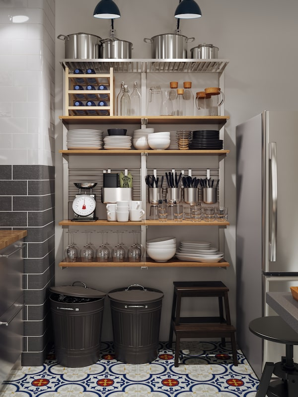 A large wall-mounted storage solution with wooden shelves and rails holding tableware, cookware and utensils.