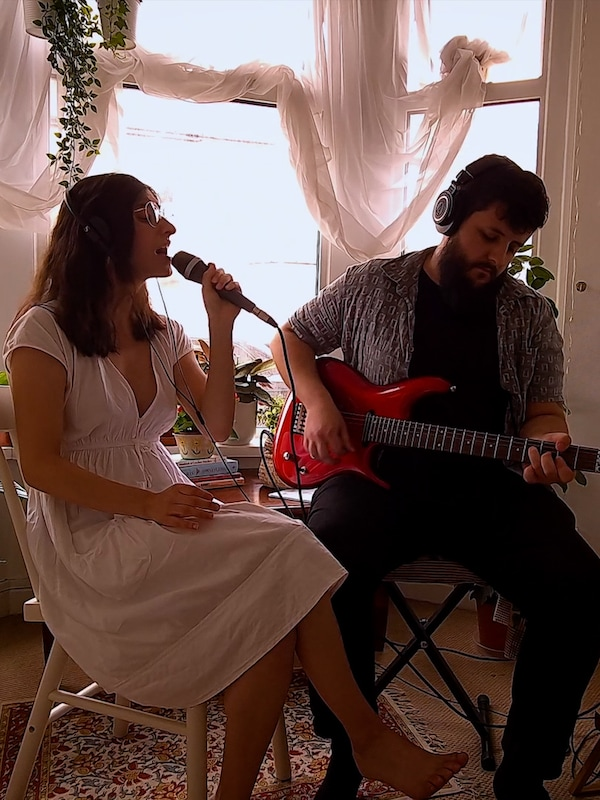 Egy nő énekel egy gitáron játszó férfivel.