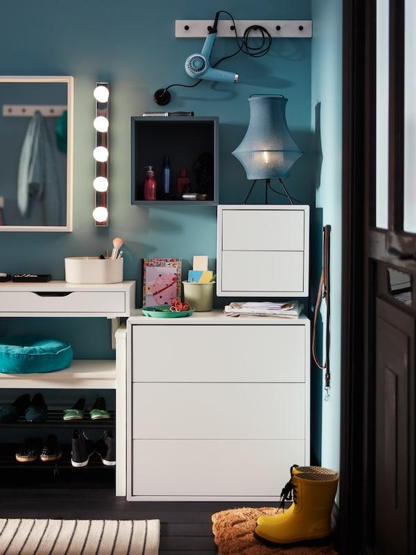 Une applique à DEL en acier inoxydable LEDSJÖ avec une étagère fixée au mur gris-turquoise EKET et des armoires blanches.