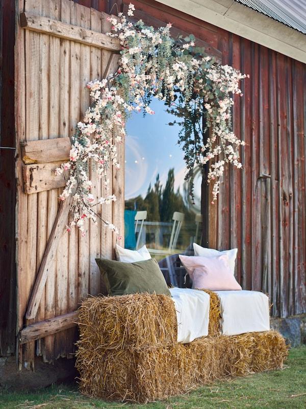 Ramas de flores artificiais SMYCKA enmarcan a porta dun celeiro e os fardos de feo úsanse como asentos con coxíns con fundas SANELA.