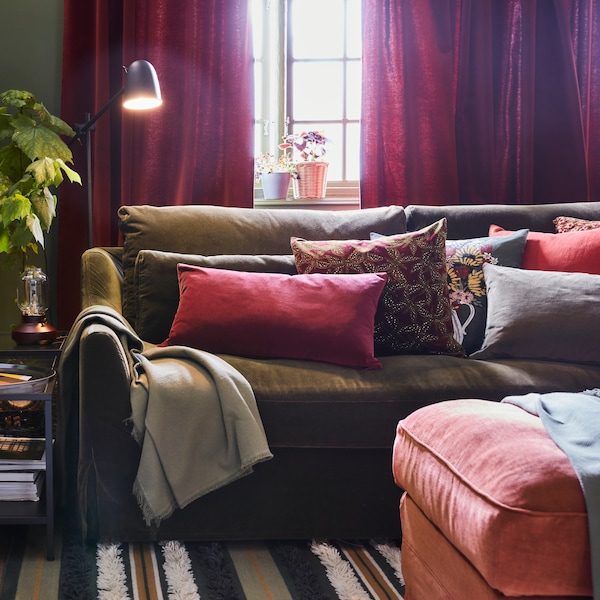A sofa in a living room with different coloured cushions, a throw is laid over one end, widows and curtains behind.