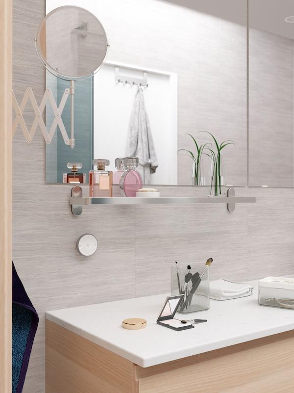 Bilik mandi berwarna kelabu dengan cermin besar, para-para BROGRUND kaca di bawah dengan dua botol minyak wangi dan vas hiasan.