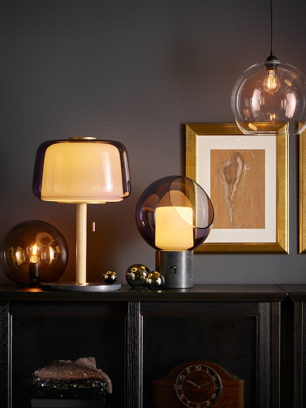 EVEDAL and FADO table lamps clustered on a cabinet, next to gold framed pictures.