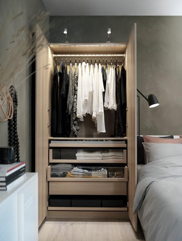 خزانة ملابس شكل خشب بلوط طلاء أبيض بإضاءة علوية مملوءة بملابس معلقة ومطوية بجوار سرير.