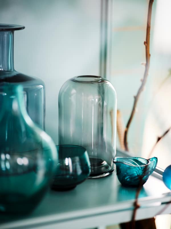 Tinted grey and blue glass vases, a candle holder and a small bowl stand on a table with some twigs in the background.