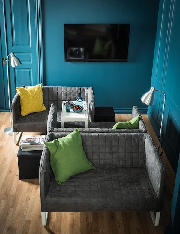 Două canapele mici așezate față în față, iar spate în spate cu una dintre ele se află o altă canapea.
