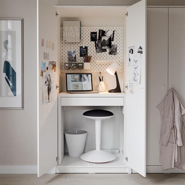 화이트 옷장 속 노트북과 조명이 놓인 미케 책상이 있고 아래에는 의자와 휴지통이 있습니다.