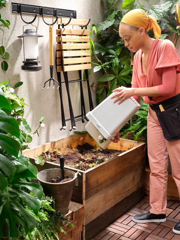 A woman empties a HÅLLBAR bin into the garden compost. Folding chairs, a lantern and a garden tool hang on hooks on a wall.