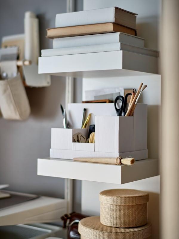 Egy fehér LACK polcos elemet látunk, rajta könyveket, kerek formájú tárolódobozokat és egy fehér TJENA íróasztali rendszerezőt, amelyben írószerek kaptak helyet.