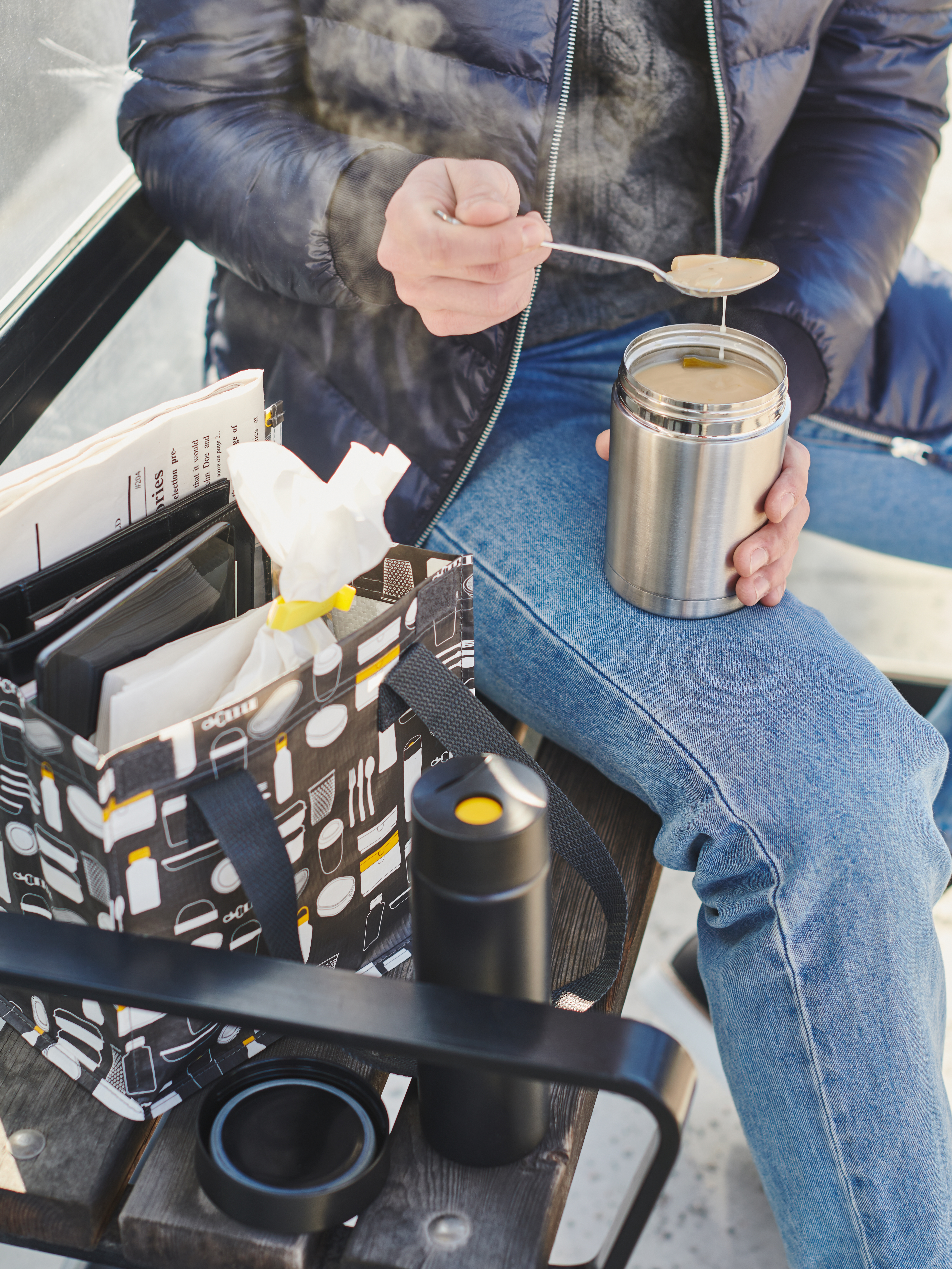 A man sitting by a FLADDRIG lunch bag on a public bench, eating with a spoon out of an EFTERFRÅGAD food vacuum flask.