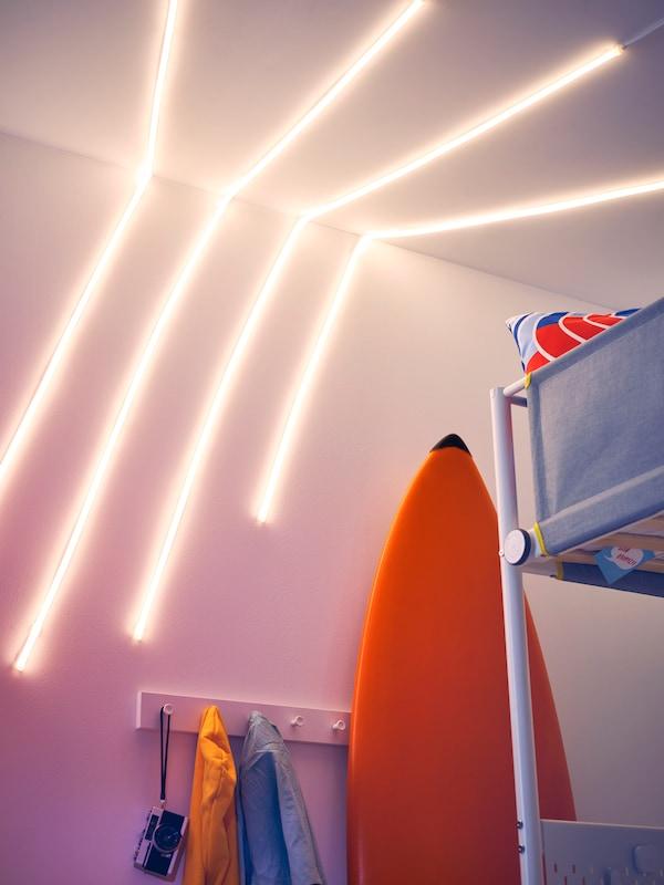 Ściana i sufit z kilkoma listwami oświetleniowymi LED MYRVARV, deska surfingowa, łóżko na antresoli, wieszak z ubraniami na hakach oraz aparat fotograficzny.