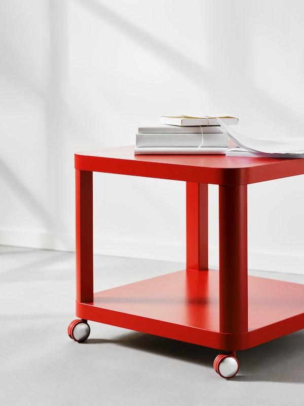 Červený odkládací stolek TINGBY na kolečkách ubílé stěny ana něm hromada knih apapírů.