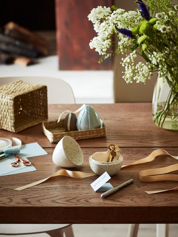 Un vaso BERÄKNA con fiori su una scrivania e uova RÅDFRÅGA, in attesa di diventare un regalo personalizzato.