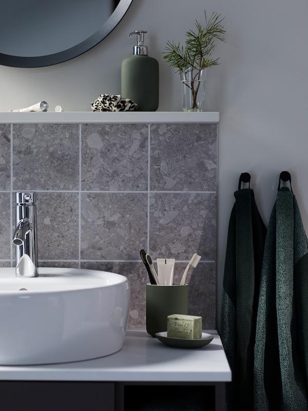 En grågrøn EKOLN sæbedispenser-, tandbørsteholder- og sæbeskålskombination ved siden af en badeværelsesvask. HIMLEÅN håndklæder hænger tæt sammen.