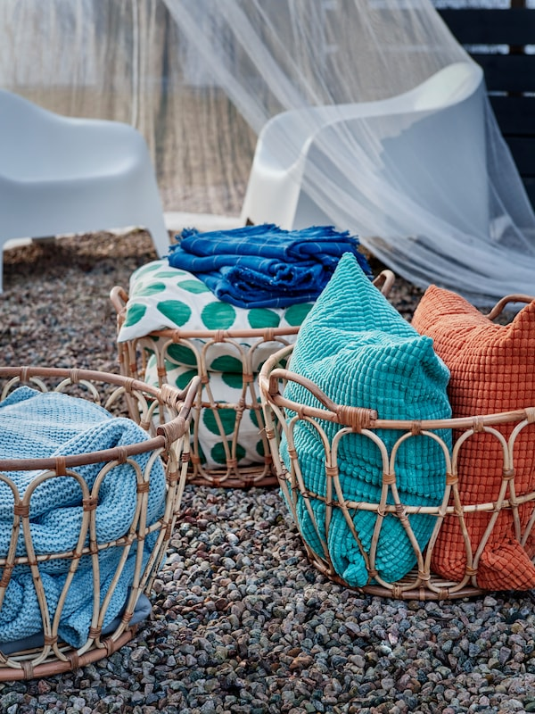 Several SNIDAD rattan baskets standing on gravel, filled with throws, cushions and other textiles.