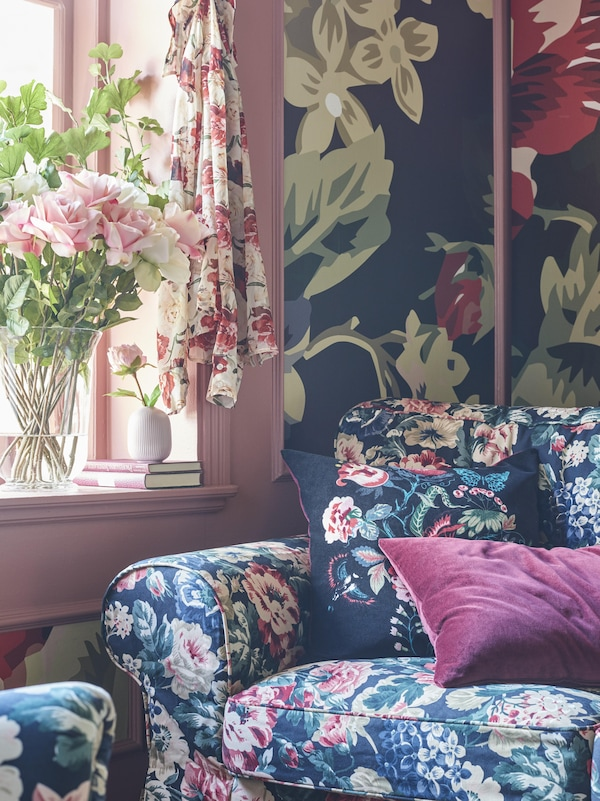 Floral patterned sofa with deep pink cushion in a room decorated with bold floral wallpaper and a pink window frame.