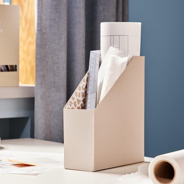 Una scrivania con un raccoglitore per riviste TJENA in carta beige con una stampa animalier bianca e marrone all'interno.