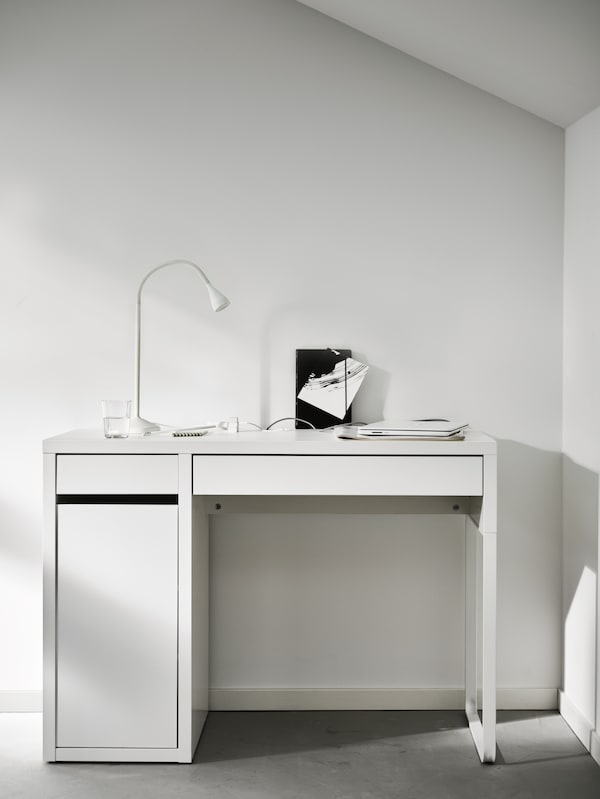 A white MICKE desk in a white room with a white NÄVLINGE LED worklamp, papers and a closed laptop on top.