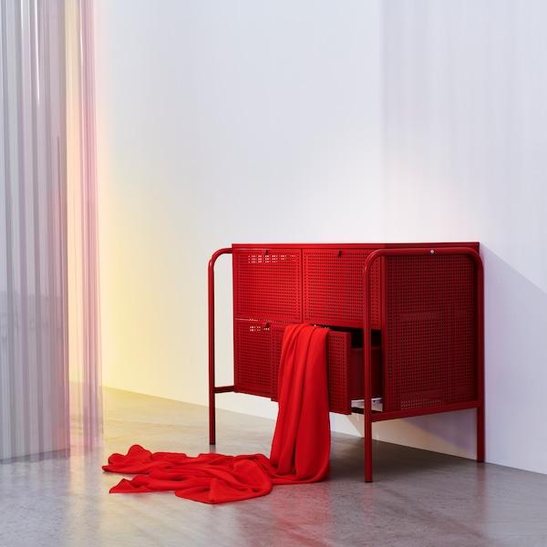 O comodă NIKKEBY roșu aprins, aflată într-o cameră goală și aerisită. O lenjerie de pat roșie este așezată decorativ, ieșind dintr-unul dintre sertare.
