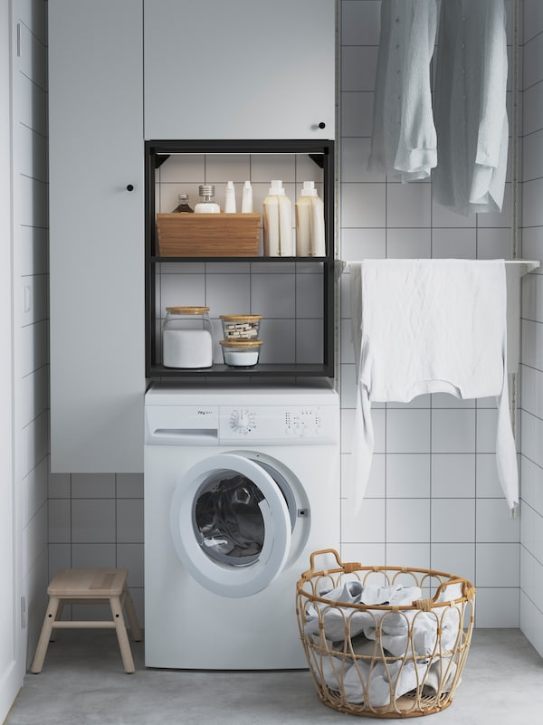 A laundry room with white tiles, laundry hanging to dry and a washing machine with an ENHET wall storage combination above.