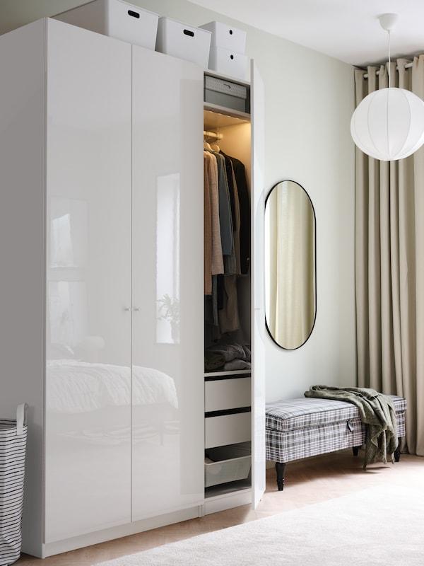 خزانات ملابس PAX بابواب بيضاء بالغة اللمعان بجوار مقعد PAX. أحد الأبواب مفتوح يظهر ملابس وأدراج بالداخل.