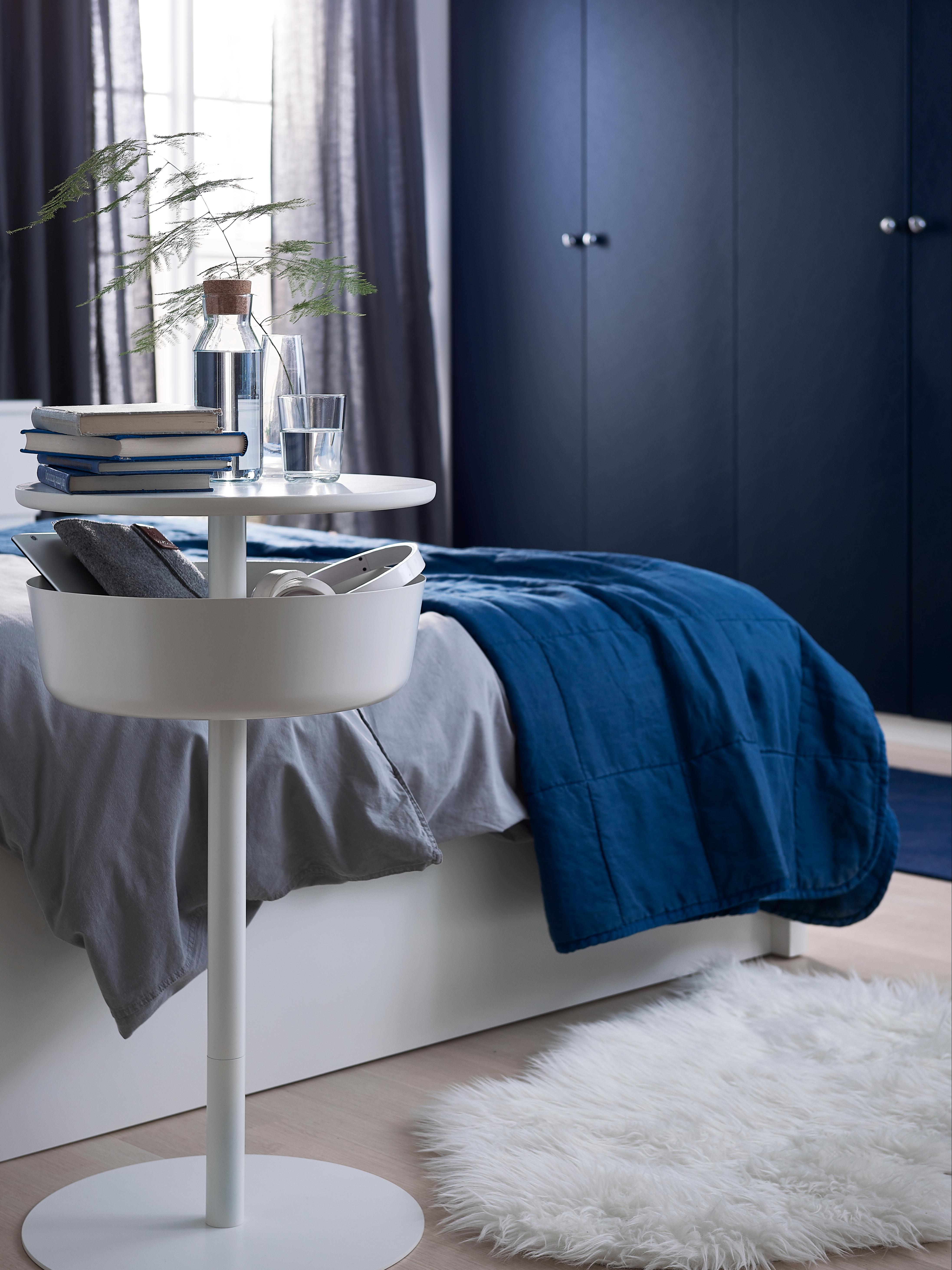 Comodino LIERSKOGEN bianco con piedistallo, piano rotondo e contenitore integrato, posizionato vicino a un letto.