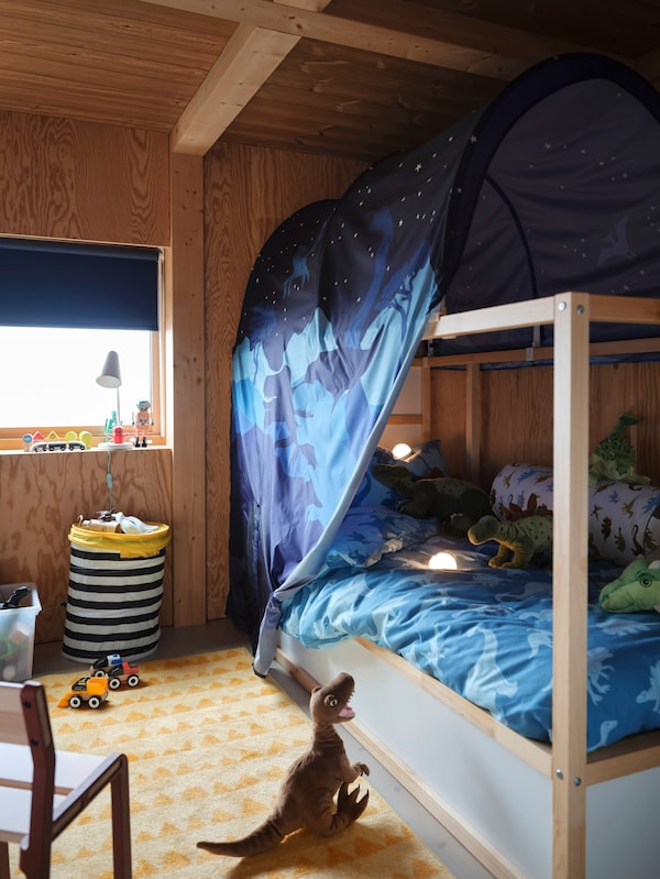 A twin bed with colourful bedding and a dinosaur-patterned canopy above the bedframe.