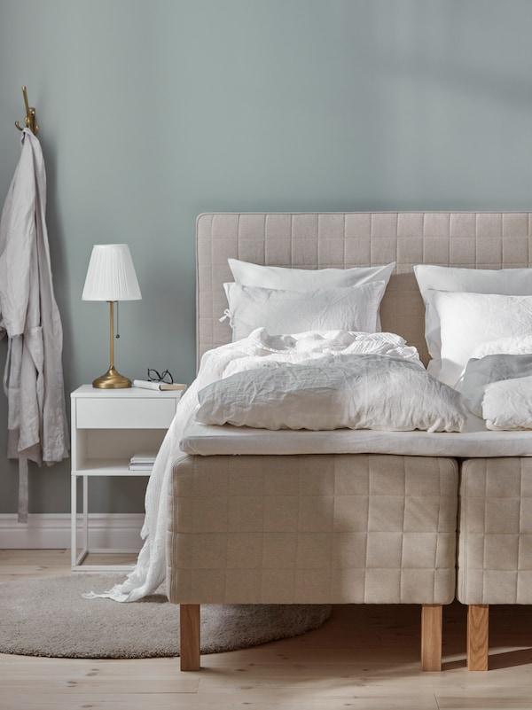 غرفة نوم بأرضيات خشبية، ومرتبة STUVLAND مع لوح رأس، وسجادة مستديرة وروب حمام معلق على خطاف على الحائط.